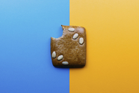 Directly above shot of eaten cookie on blue and yellow background 11016035654| 写真素材・ストックフォト・画像・イラスト素材|アマナイメージズ