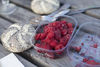 Raspberries in container by bread roll on table 11016035954| 写真素材・ストックフォト・画像・イラスト素材|アマナイメージズ