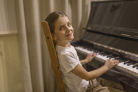 Side view portrait of cute girl playing piano at home 11016036011| 写真素材・ストックフォト・画像・イラスト素材|アマナイメージズ