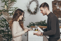 Side view of smiling couple packing Christmas gifts at home 11016036133| 写真素材・ストックフォト・画像・イラスト素材|アマナイメージズ