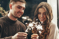 Smiling couple playing with sparklers during Christmas celebration 11016036134| 写真素材・ストックフォト・画像・イラスト素材|アマナイメージズ