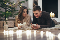 Smiling couple having coffee while lying on rug at home during Christmas 11016036136| 写真素材・ストックフォト・画像・イラスト素材|アマナイメージズ