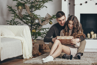 Young couple looking at gift box while sitting on rug at home during Christmas 11016036138| 写真素材・ストックフォト・画像・イラスト素材|アマナイメージズ