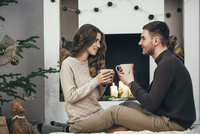 Smiling couple having coffee while sitting on rug at home during Christmas 11016036139| 写真素材・ストックフォト・画像・イラスト素材|アマナイメージズ