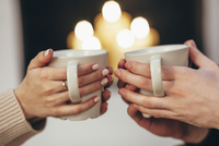 Cropped image of couple holding coffee cups against illuminated candles at home 11016036140| 写真素材・ストックフォト・画像・イラスト素材|アマナイメージズ