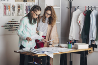 Fashion designer and female trainee looking at sketch at workbench in studio 11016036146| 写真素材・ストックフォト・画像・イラスト素材|アマナイメージズ