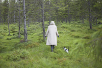 Rear view of woman wearing long coat while walking with cat on grassy field 11016036224| 写真素材・ストックフォト・画像・イラスト素材|アマナイメージズ