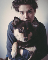 Portrait of confident woman embracing dog against gray background 11016036227| 写真素材・ストックフォト・画像・イラスト素材|アマナイメージズ