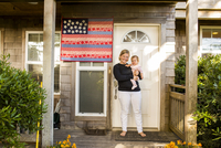 Caucasian mother holding baby daughter on front porch 11018056220| 写真素材・ストックフォト・画像・イラスト素材|アマナイメージズ