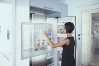 Mixed race girl using hologram refrigerator touch screen in kitchen 11018070737| 写真素材・ストックフォト・画像・イラスト素材|アマナイメージズ
