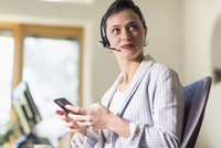Businesswoman using cell phone and headset in office 11018073710| 写真素材・ストックフォト・画像・イラスト素材|アマナイメージズ