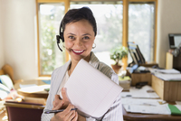 Businesswoman using notepad and headset in office 11018073718| 写真素材・ストックフォト・画像・イラスト素材|アマナイメージズ