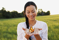 Asian woman holding butterfly in hands 11018074296| 写真素材・ストックフォト・画像・イラスト素材|アマナイメージズ
