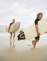 Mother and son carrying surfboards out of water at beach 11018074351| 写真素材・ストックフォト・画像・イラスト素材|アマナイメージズ