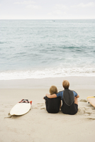 Mother and son sitting on beach next to surfboard 11018074352| 写真素材・ストックフォト・画像・イラスト素材|アマナイメージズ