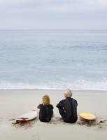 Father and son sitting on beach with surfboards 11018074365| 写真素材・ストックフォト・画像・イラスト素材|アマナイメージズ