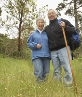 Senior Asian couple with backpack and walking stick outdoors 11018074395| 写真素材・ストックフォト・画像・イラスト素材|アマナイメージズ