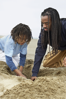 African father and son digging in sand 11018074554| 写真素材・ストックフォト・画像・イラスト素材|アマナイメージズ