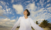 Asian woman walking under blue sky with clouds 11018074575| 写真素材・ストックフォト・画像・イラスト素材|アマナイメージズ