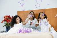 Hispanic mother and daughters throwing feathers in bedroom 11018077678| 写真素材・ストックフォト・画像・イラスト素材|アマナイメージズ