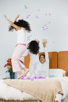 Hispanic mother and daughters throwing feathers in bedroom 11018077679| 写真素材・ストックフォト・画像・イラスト素材|アマナイメージズ