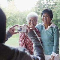 Japanese girl taking photograph of mother and grandmother 11018078384| 写真素材・ストックフォト・画像・イラスト素材|アマナイメージズ