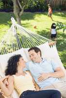 Couple in hammock with children playing in background 11018079114| 写真素材・ストックフォト・画像・イラスト素材|アマナイメージズ