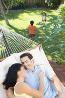 Couple relaxing in hammock with children playing in background 11018079117| 写真素材・ストックフォト・画像・イラスト素材|アマナイメージズ