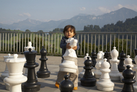 Mixed race boy playing with large chess pieces 11018079483| 写真素材・ストックフォト・画像・イラスト素材|アマナイメージズ
