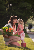 Caucasian mother holding flowers and kissing daughter 11018079759| 写真素材・ストックフォト・画像・イラスト素材|アマナイメージズ