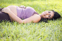 Mixed race pregnant woman laying in grass 11018080397| 写真素材・ストックフォト・画像・イラスト素材|アマナイメージズ