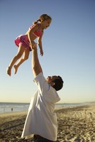 Father lifting daughter in air on beach 11018080564| 写真素材・ストックフォト・画像・イラスト素材|アマナイメージズ
