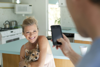 Man taking picture of wife holding dog in kitchen 11018080713| 写真素材・ストックフォト・画像・イラスト素材|アマナイメージズ