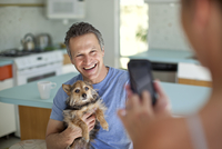 Woman taking picture of husband holding dog in kitchen 11018080714| 写真素材・ストックフォト・画像・イラスト素材|アマナイメージズ