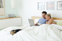 Couple using laptop together in bed 11018080715| 写真素材・ストックフォト・画像・イラスト素材|アマナイメージズ