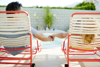 Couple holding hands in lounge chair near swimming pool 11018080733| 写真素材・ストックフォト・画像・イラスト素材|アマナイメージズ
