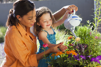 Mixed race mother and daughter watering flowers 11018080905| 写真素材・ストックフォト・画像・イラスト素材|アマナイメージズ