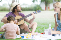 Man playing acoustic guitar next to wife and son 11025010135| 写真素材・ストックフォト・画像・イラスト素材|アマナイメージズ