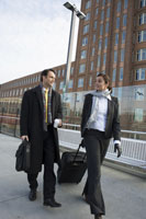 Businesspeople walking with suitcases 11029002458| 写真素材・ストックフォト・画像・イラスト素材|アマナイメージズ