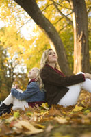 Mother and daughter sitting in park 11029005592| 写真素材・ストックフォト・画像・イラスト素材|アマナイメージズ