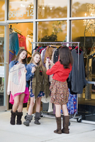 Pre-teen girls shopping for clothes and taking picture with smartphone 11030039061| 写真素材・ストックフォト・画像・イラスト素材|アマナイメージズ