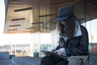 Teenage girl sitting outdoors at train station, wearing fedora and looking at tablet computer, Mannheim, Germany 11030041009| 写真素材・ストックフォト・画像・イラスト素材|アマナイメージズ