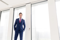 Portrait of confident young businessman standing with hands in pockets against office window 11044034806| 写真素材・ストックフォト・画像・イラスト素材|アマナイメージズ