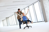 Full length of young businessman pushing female colleague in chair at empty office 11044035006| 写真素材・ストックフォト・画像・イラスト素材|アマナイメージズ