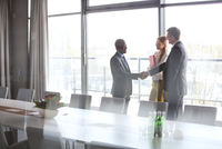 Businessmen shaking hands by female colleague in conference room at office 11044035035| 写真素材・ストックフォト・画像・イラスト素材|アマナイメージズ