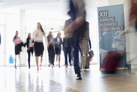 Blurred motion of business people walking in convention center 11044035208| 写真素材・ストックフォト・画像・イラスト素材|アマナイメージズ