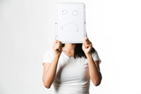 Chinese woman holding up a white board with a sad face drawn on it 11044035925| 写真素材・ストックフォト・画像・イラスト素材|アマナイメージズ