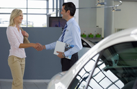 Car salesman shaking hands with female customer in showroom, man holding brochure, smiling, profile 11080004016| 写真素材・ストックフォト・画像・イラスト素材|アマナイメージズ