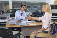 Car salesman and female customer sitting at desk in large car showroom, shaking hands, smiling 11080004024| 写真素材・ストックフォト・画像・イラスト素材|アマナイメージズ