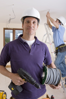 Electrician holding cable spool and drill with co-worker wiring ceiling in background 11080006874| 写真素材・ストックフォト・画像・イラスト素材|アマナイメージズ